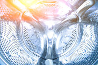 inside the drum of the washing machine. Steel drum open. Closeup. washing machine drum background with copyspace showing household concept.