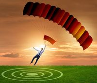 Young businessman falling on parachute in business concept