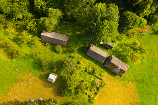 Aerial drone view of old wooden hut on mountain slope. Stable for cattle and barn near hut, green