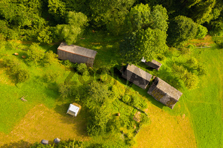 Aerial drone view of old wooden hut on mountain slope. Stable for cattle and barn near hut, green well-groomed yard