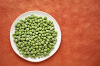 frozen green peas on a white plate