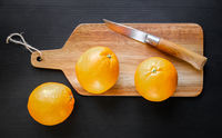 Oranges and old traditional pocket knife on a cutting board