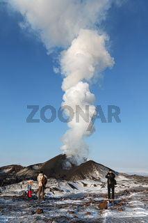 Tourists watching eruption volcano Kamchatka, erupting from crater lava, steam, gas and ash