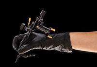 Tattoo machine in artist's hand