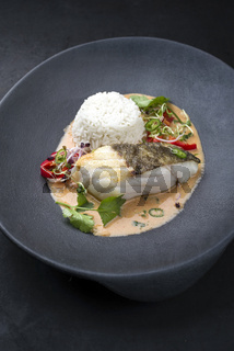Gourmet fried skrei cod fish Thai curry with jasmine rice and chili as closeup on a modern design plate with copy space