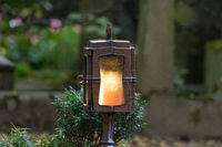 Grave lantern with burning candle in a cemetery