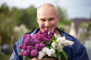 Elderly man with a bouquet of flowers. Brutal gray-haired man with a beautiful lilac.