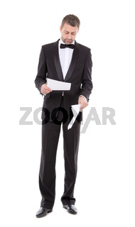 Man in a tuxedo reading the document