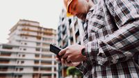 Inclusion of mobile applications in the development management process. Caucasian engineer builder in hard hat use on construction site mobile phone, engineer at work checking building project