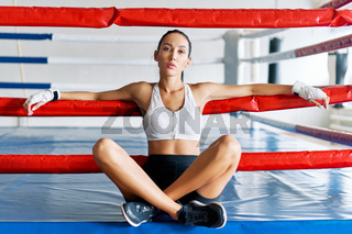 Young beautiful woman relax sitiing in boxing ring after hard workout
