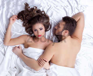 Pair of handsome young lovers lying on silk sheets