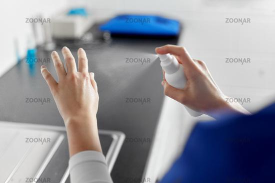doctor or nurse spraying hand sanitizer