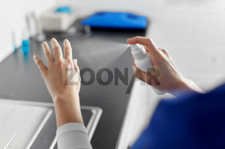 doctor or nurse spraying hand sanitizer