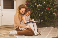 Story time with mother and daughter near Christmas tree