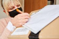 Frau mit Mundschutz vor Wohnungstür gibt Lieferdienst Unterschrift