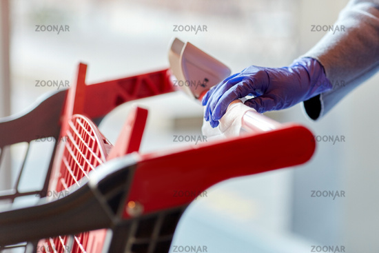 hand cleaning shopping cart handle with wet wipe