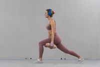 Stretching using dumbbells with hands down young girl losing weight at home wearing pink outfit while listen music in blue wireless headphones. Sport and recreation concept