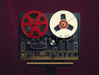 Vintage Reel tape recorder on a red background. A symbol of recording in retro style