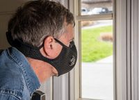 Senior man with face mask peering through front door window for visitors during quarantine