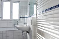 Waschbecken in hellem Bad mit Heizkörper und Fenster