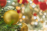 Blur bokeh background of Christmas tree ornament lights with yellow decoration balls in foreground