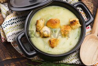 Creamy Jerusalem artichoke soup on wooden background