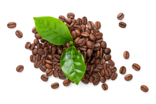 Pile Of Coffee Beans With Green Leaves
