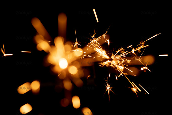 Burning sparkler and spots of light against black background