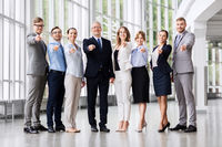 business people pointing to camera at office