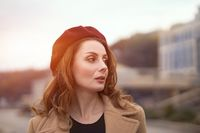 Charming pretty french woman in an autumn beige coat and red beret standing outdoors with urban city background. Tinted photo