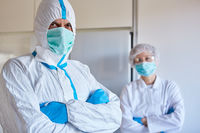 Arzt und Pfleger in Klinik mit Schutzkleidung