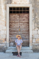 Beautiful young female tourist woman sitting and resting on vinatage wooden doorstep and textured stone wall at old Mediterranean town, smiling, holding, using smart phone to network on vacationes