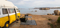 Old colorful retro camper van on camping site at beautiful rocky coastal landscape of Costa Smeralda, north east Sardinia, Italy. Tourism vacation and travel.