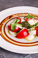 Caprese salad with mozzarella, tomato, basil and pesto