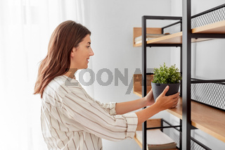 woman decorating home with flower or houseplant