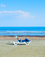 Lonely woman beach deckchair Cyprus