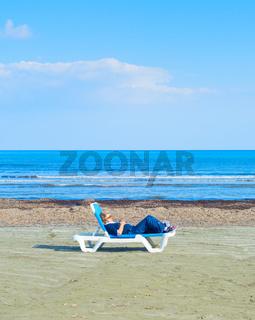 Lonely woman beach deckchair Cyprus