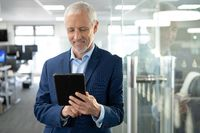 Senior businessman using digital tablet at modern office