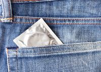 A condom pops out of the front pocket of a pair of jeans