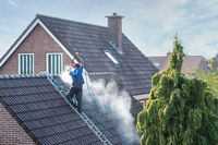 Cleaner with pressure washer at roof house cleaning roof tiles
