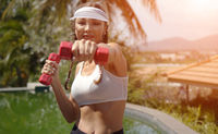 Cheerful woman exercising with dumbbells near swimming pool