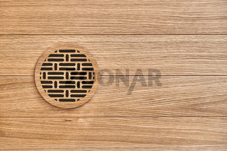 Wooden round vent cover in wooden ceiling of house