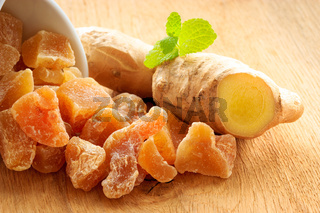 Closeup root and candied ginger on wooden table