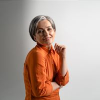 Portrait of a mature grey haired woman wearing orange shirt happily smiling on camera. Pretty mid aged grey haired woman in orange shirt isolated on grey background