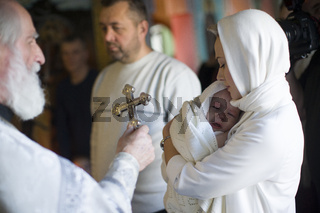 Belarus, Gomel, January 19, 2019. Prudkovsky church. Baptism of the child. Godmother with a baby and priest with a cross. Acceptance of faith.