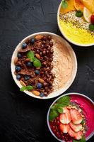 Various healthy fresh smoothies or yogurts in bowls. With strawberries, kiwi, chia, blackberries