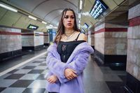 Fashion model girl in purple synthetic fur coat standing bared her shoulders in the walking subway passage platform. Female with luxury makeup, long hair in stylish outfit