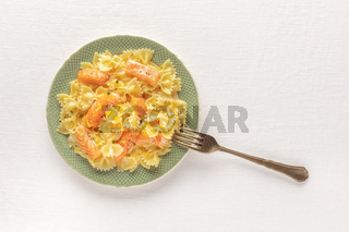 An overhead photo of a plate of salmon pasta, Farfalle with smoked salmon and cream sauce, shot from the top on a white table cloth