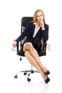 Beautiful caucasian business woman is sitting on a chair with her legs stretched.