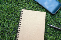 Kraft paper spiral notebook with pen on the Artificial turf